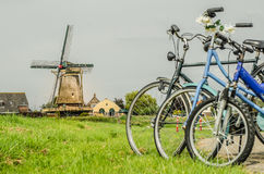 Three bicycles with windmill. Family with bicycles on the picnic in a Dutch village meadow with windmill on the background, focus on windmill Royalty Free Stock Image