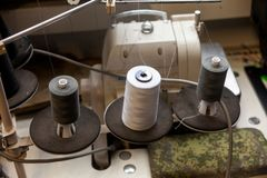 Three big black and white bobbins with large mating threads mounted on a rod near the sewing machine on the table of the workshop stock images
