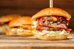 Free Three Big Burger With Meat Cooked On BBQ Coal. Lunch On A Wooden Background. The Concept Of Fast Food And Unhealthy Food Royalty Free Stock Photo - 144861015