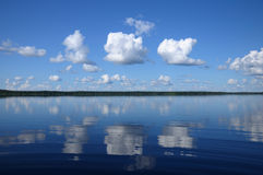 Three big clouds above the mirrored lake. The picture shows typical landscape in the south region of Karelia - blue sky, clouds, big lake looks like a mirror and royalty free stock images