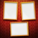 Three big frames on vintage background. Three big picture frames in gold on red vintage background Stock Photography