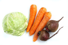 Three big  fresh carrots, the cabbage and beets. Three big  fresh carrots,  the heads of cabbage and two beets on the  table Royalty Free Stock Photo