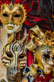 Three Bightly Colored and Feathered Masks in Venice Venezia It. A trio of brightly colored Venetian Masks with feathers at an outdoor stall in Venice, Italy Stock Photos
