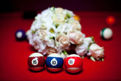 Three billiard balls stand in a row on a red table. Stock Images