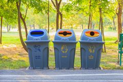Three bins for waste sorting along the way in the park . Three gray plastic bins for waste sorting along the way in the park with nature background stock photo