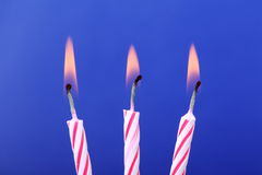 Three Birthday Candles. Three read and white birthday cake or celebration candles on a blue background Royalty Free Stock Image