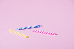 Three birthday candles. Laying on rose background Royalty Free Stock Photos
