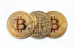 Three Bitcoin cryptocurrency coins lie in a row, you can see both sides. Close-up royalty free stock image