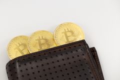 Three Bitcoin tokens coming out of a wallet, on white background. royalty free stock image