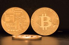 Three Bitcoins, two standing and showing both sides of the coins. One is lying on a black underground. Symbols for new virtual currency stock images