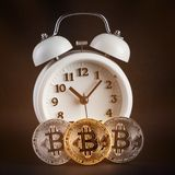 Three bitcoins and vintage white alarm clock glowing on black background. Stock Photography