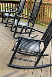 Three black Adirondack rocking chairs. On old wood porch invite people to sit and relax for a spell Stock Photography