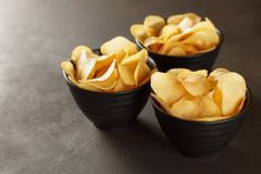 Three black bowl with potato chips on dark background. Stock Photos