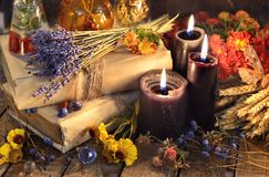 Three black candles, lavender bunch, healing herbs and flowers on planks. Occult, esoteric, divination and wicca concept. Vintage background royalty free stock photography