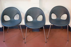 Three black chairs. Three empty alien-like looking black chairs in a waiting room Stock Images