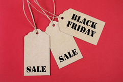 Three Black Friday Sale Tags. Black Friday Sale message sign on brown paper sale tags on red background Stock Photography