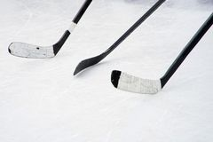 Three black ice hockey sticks on the court. Preparation for training in an open area. Winter sports royalty free stock photography