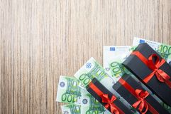 Three black gift box with a bow with euro banknotes on a wooden table. top view, copy space stock image