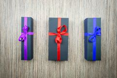 Three black gift boxes with a bow on a wooden table royalty free stock photos
