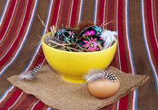 Black painted Easter eggs yellow soup plate straw Stock Images