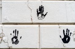 3 three black palm imprints on white large bricks with white peeling paint - high quality texture / background royalty free stock images
