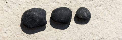 Three black pebbles on a white surface Royalty Free Stock Image