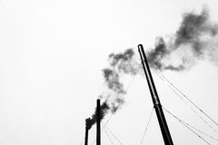 The three black pipes and black smoke on a light gray background Royalty Free Stock Photo