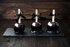 Three black poison caramel apples. Traditional dessert recipe for Halloween party Royalty Free Stock Photos