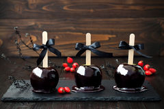 Three black poison caramel apples. Traditional dessert recipe for Halloween party. Selective focus Stock Images
