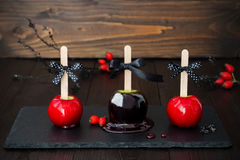 Three black and red poison caramel apples. Traditional dessert recipe for Halloween party. Royalty Free Stock Photography