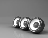 Three black speakers on grey background Stock Photos
