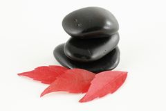 Three black stones with red leaves. Three stacked black stones isolated on a white background Royalty Free Stock Photo