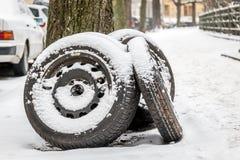 Three black tires in a snowy street Stock Photo