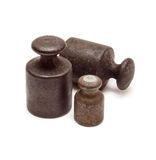 Three black weights. Set of three black antique calibration weights, isolated on white background Royalty Free Stock Image