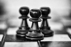 Three black wooden pawns on chess board stock photos