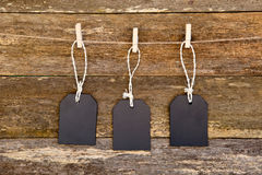 Three blackboard tags with string hanging against rustic timber Royalty Free Stock Photography