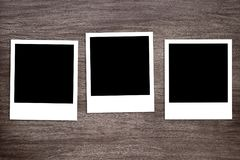 Three blacked-out instant photo print templates on wooden background Stock Image