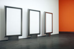 Three blank billboards. In room with black floor, whte and orange walls. Mock up, 3D Rendering Royalty Free Stock Photo