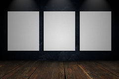 Three blank canvas on a concrete wall Stock Image