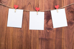 Three blank card on clothespins with hearts. Mockup for text on the wooden background. For Valentines Day greetings and Royalty Free Stock Images