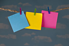 Three blank colorful notes clipped on twine clothesline with clothespins in front of beautiful blue sky. Stock Photos