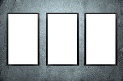 Three blank frames on concrete wall. Stock Photos