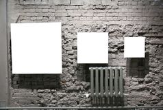 Three blank frames on grey brick wall stock images
