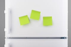 Three blank green sticky paper notes on white refrigerator Stock Images