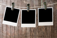 Three blank instant photos hanging on the clothesline Royalty Free Stock Photo