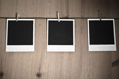 Three blank instant photos hanging on clothesline on wooden background, art concept Stock Images