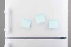 Three blank light blue sticky paper notes on white refrigerator Stock Image