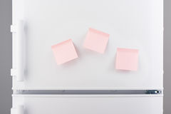 Three blank light pink sticky paper notes on white refrigerator Royalty Free Stock Image