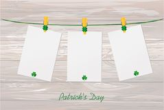 Three blank paper with green clovers hanging on a rope on a wood Stock Images