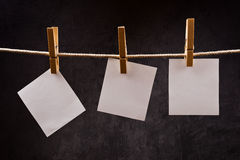 Three Blank paper notes hanging on rope with clothes pins Royalty Free Stock Image